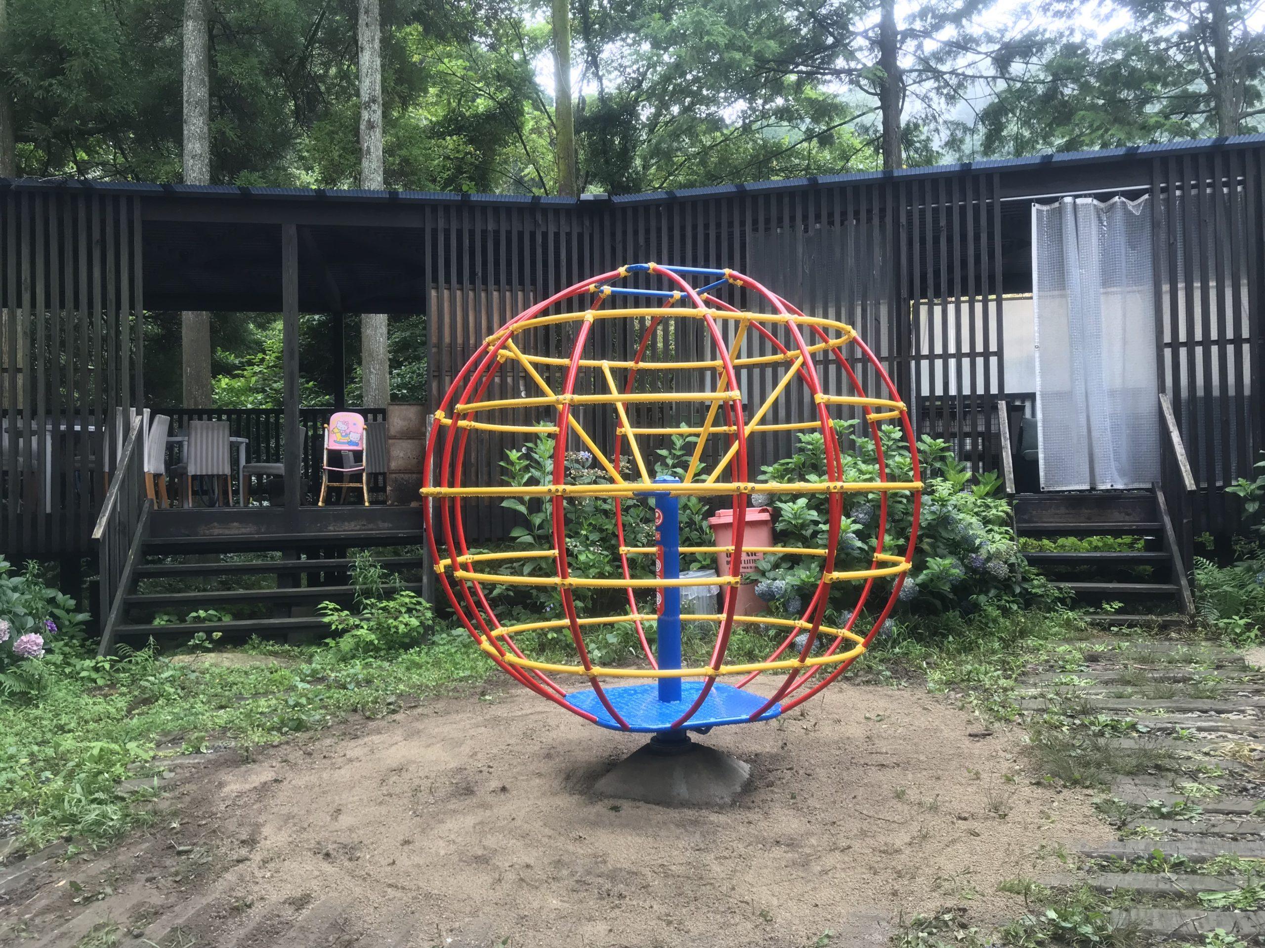 公園 回転ジャングルジム 中心軸と台が青 円形部分が赤と黄色のパイプ